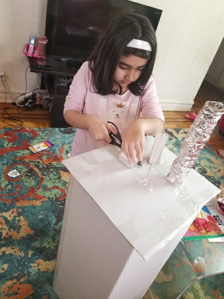 girl cuts out the pieces for her project