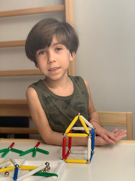 boy wearing a tank top sits near his creation