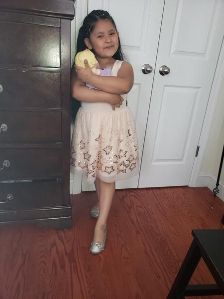 child in a dress hugs her stuffed animal