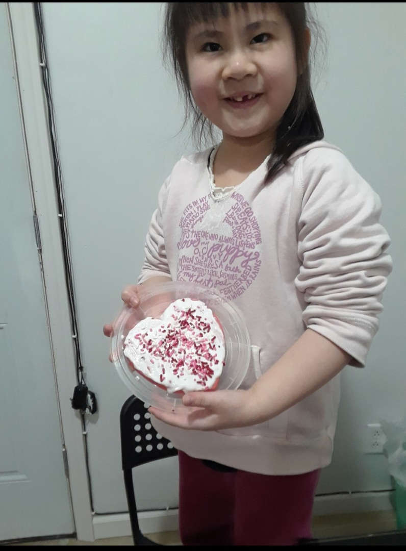 child holds up her heart cookie for a picture