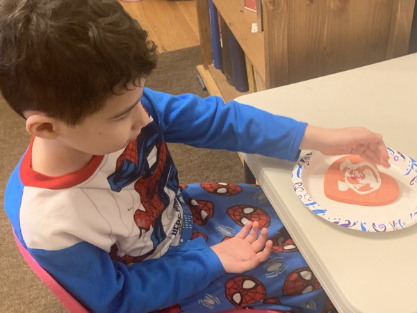 child puts sprinkles on his heart cookie