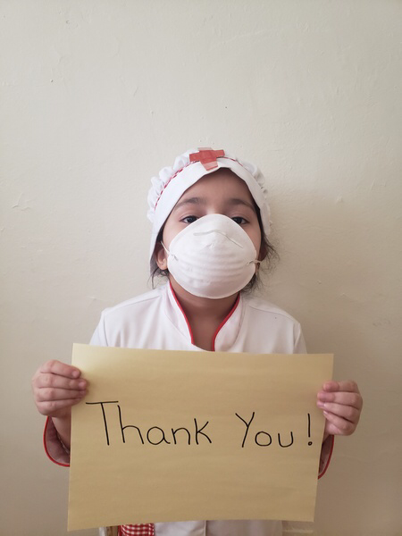 child wears a mask holding a thank you sign