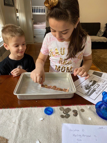 the siblings are excited to put the pennies on their boat