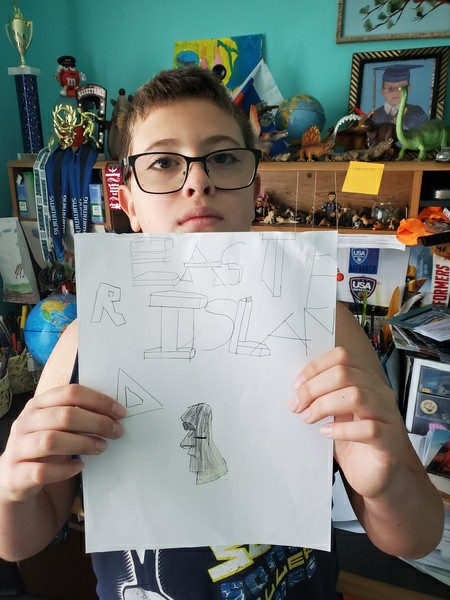 boy holds up his writing and drawing