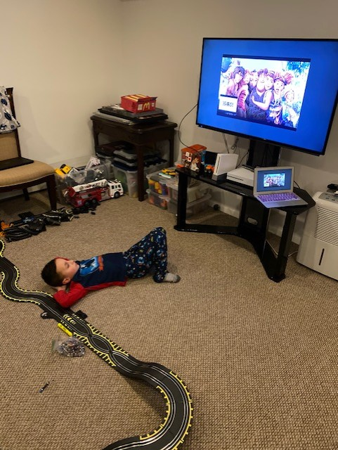 boy laying on the floor watching a movie