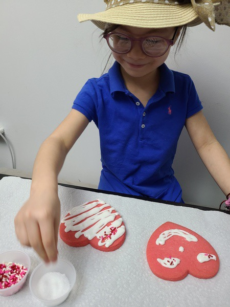 student in blue shirt decorating their heart shaped cookies