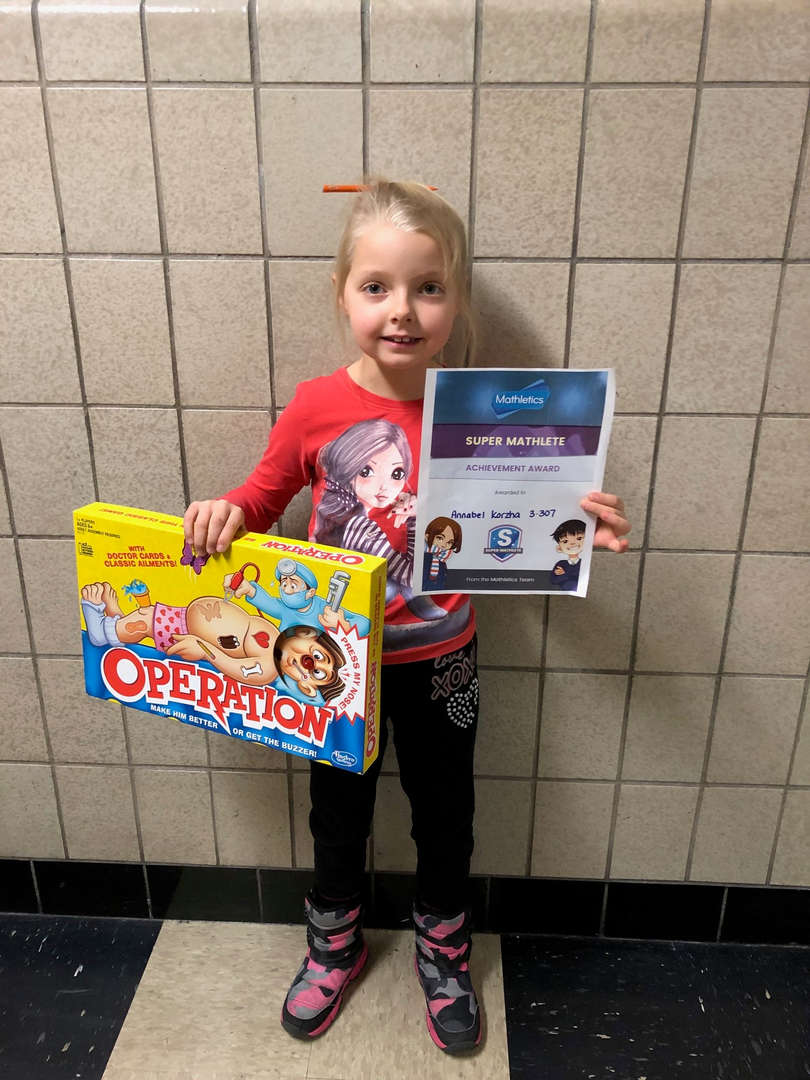 Student holding Operation board game and certificate.