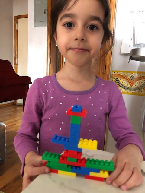 Girls shows her Lego building