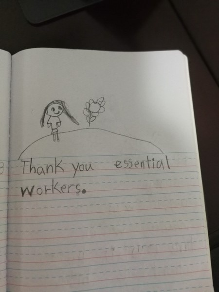 child writes thank you essential workers