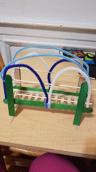 bridge made of popsicle sticks, construction paper and pipe cleaners