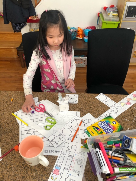 child uses paper, scissors and markers to make a board game