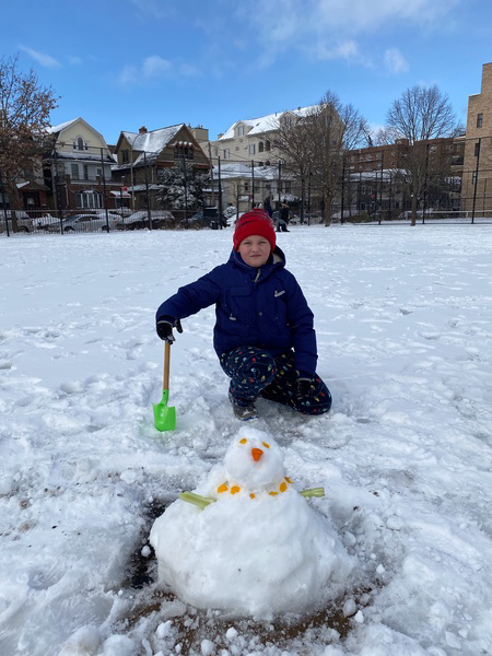 boy with a shovel building a snowman