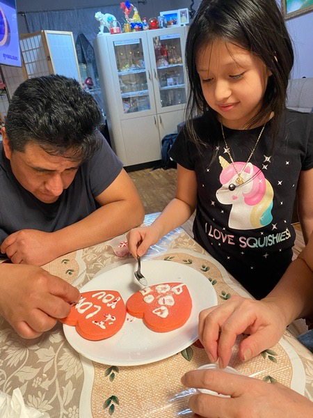 father and daughter decorate a cookie