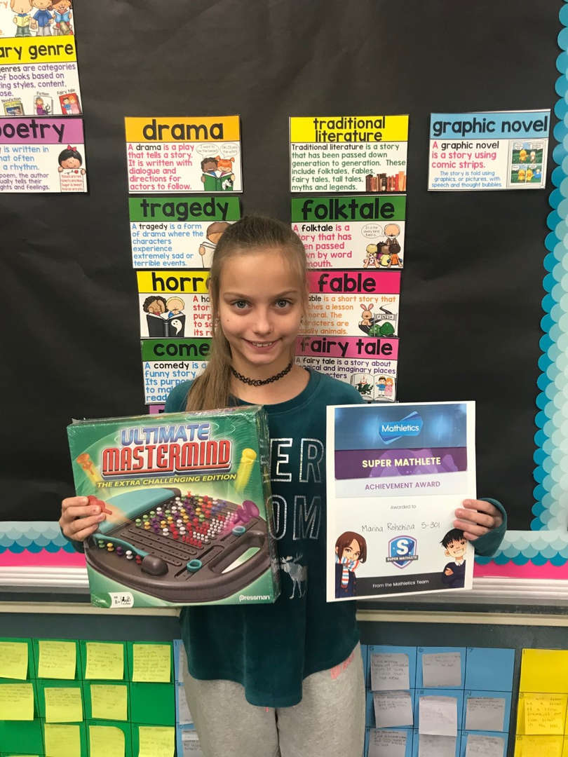 A fifth grade student holds her certificate and prize for Mathletics!