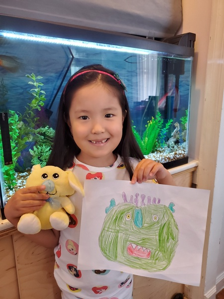 child holds monster and stuffed animal in front of a fish tank