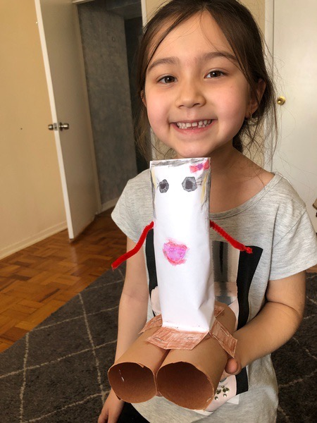 girl holds the paper towel roll doll she made