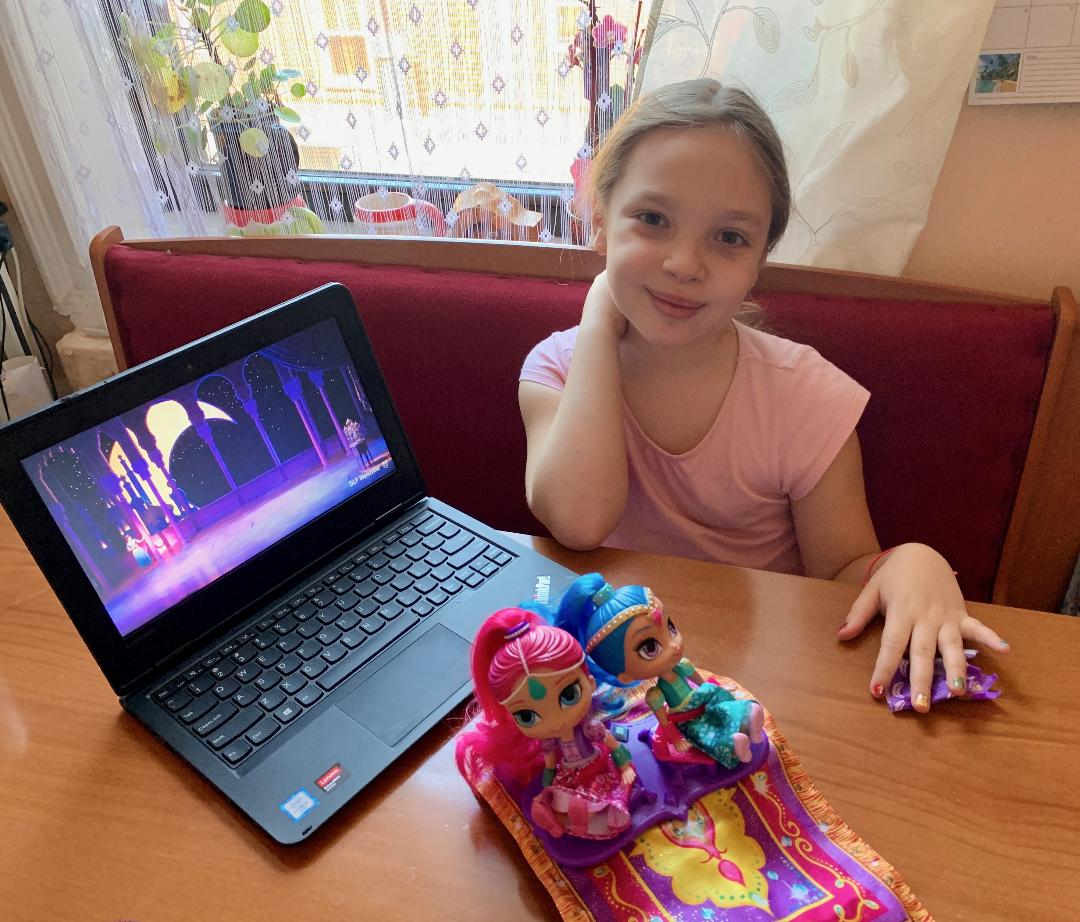 girl sits at the table with her laptop
