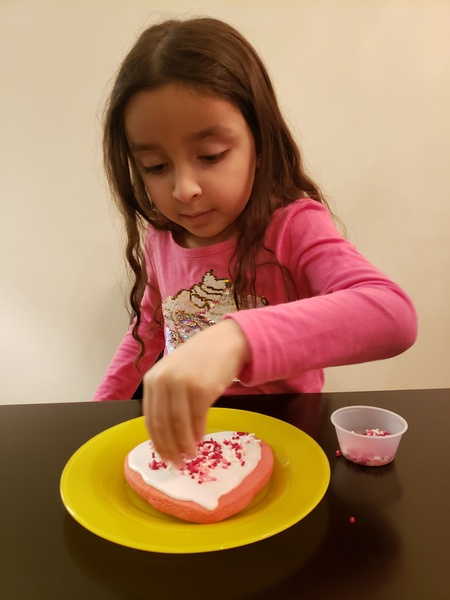 girl in dark pink shirt putting sprinkles on her cookie