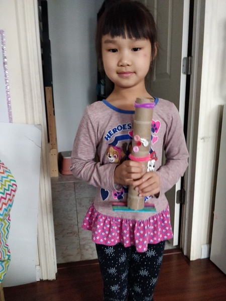 the girl holds her paper towel creation with both hands