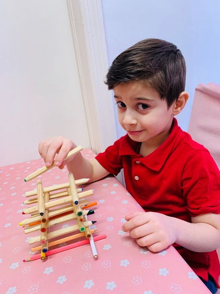 child in a red shirt builds using popsicle sticks