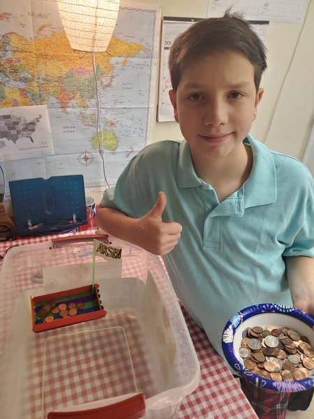 the child gives a thumbs up because his boat carries the pennies