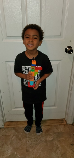child holds his lego creation