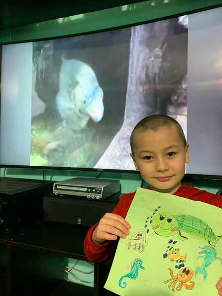 boy holding artwork in front of the TV