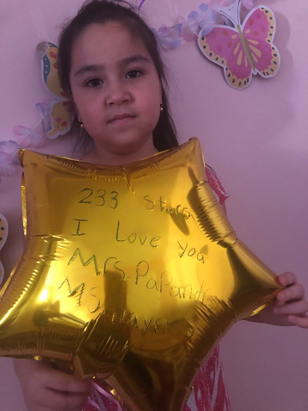 girl holds a balloon with writing