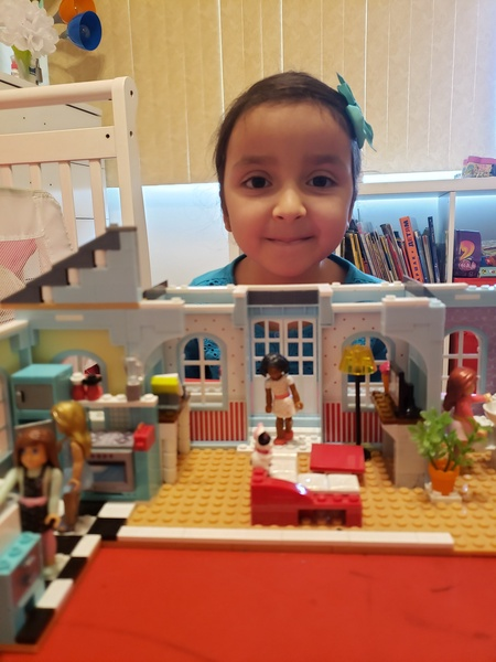 child hold the lego house