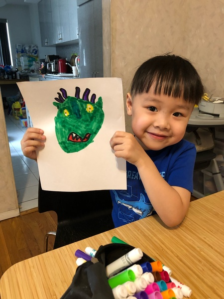 child holds his drawing from the pajama party
