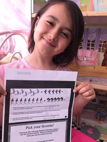 girl holds a printout with head tilted