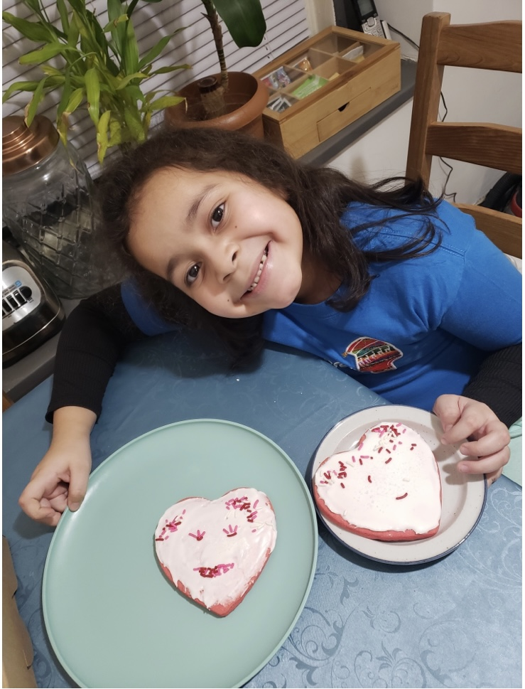 student smiling and showing her two decorated cookies