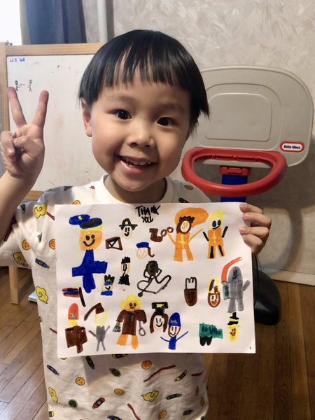 child gives a peace sign while holding his artwork
