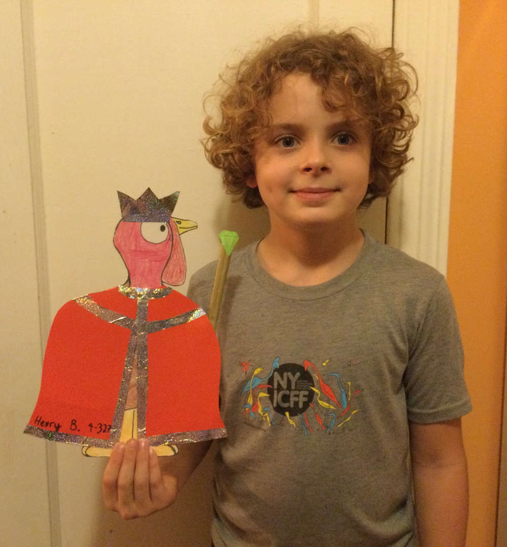 Child holding a turkey dressed as a king with a red cape.