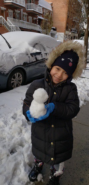 boy carrying a small snowman