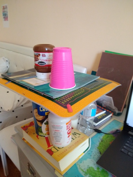 the child made a tower using cups and cardboard