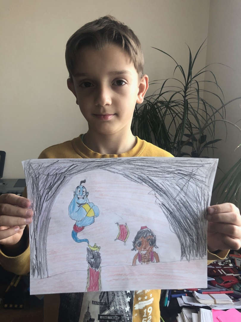 boy in yellow shirt holds his picture