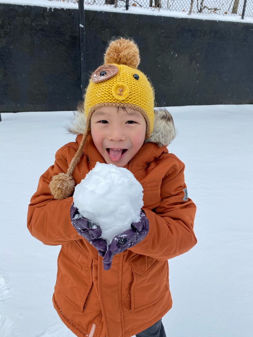 child pretending to eat the snow