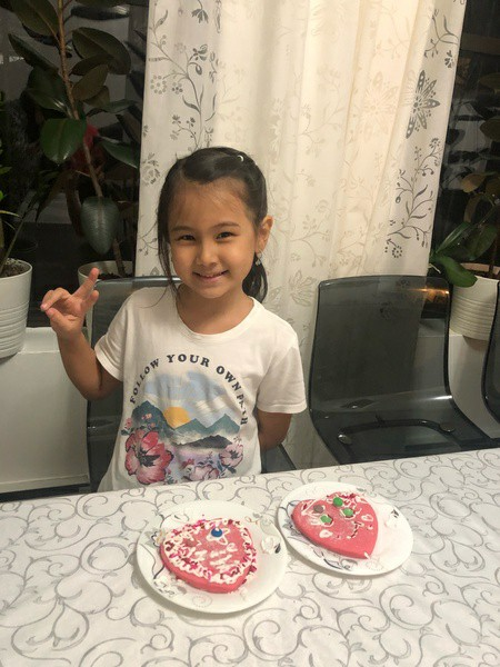 girl giving peace sign and showing her decorated cookies