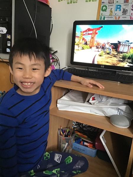 Boy, with a large smile enjoys his  virtual trip to Lego Land