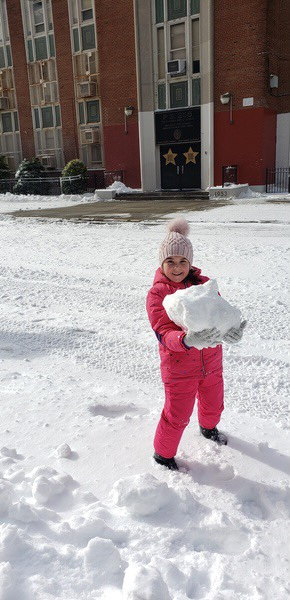 girl carrying a large snowball
