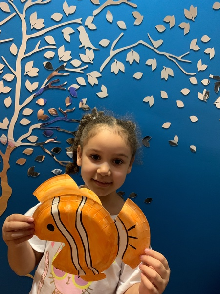 girl holding paper plate clownfish