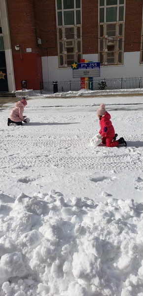 children playing in the snow and building a snowman