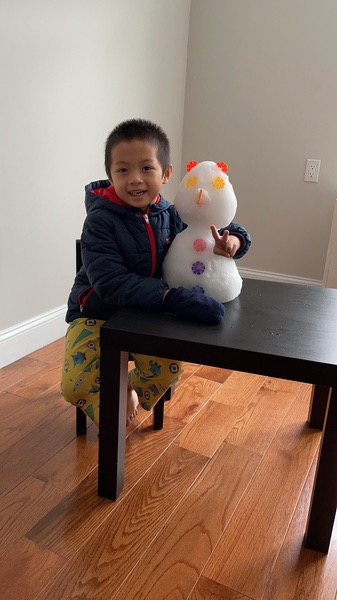 boy wearing a jacket inside with snowman