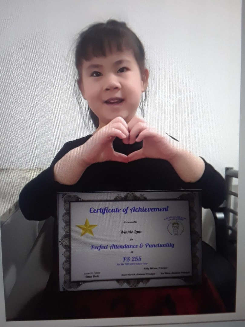 girl has her certificate while making a heart with her hands