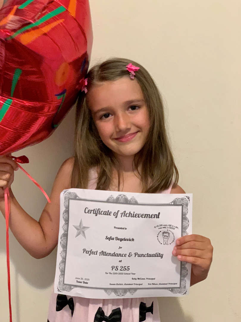 child holds her certificate and balloon
