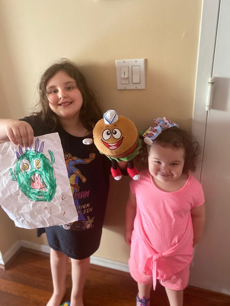 two sisters stand together with the monster picture and stuffed animal
