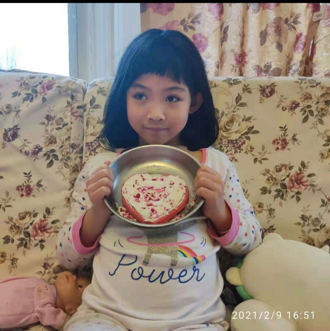 child shows her decorated cookie on a plate