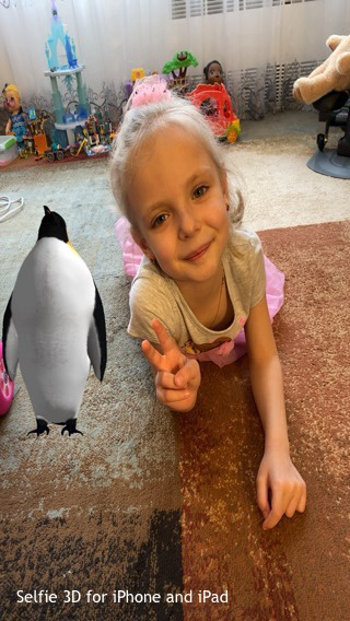 child gives a peace sign next to a penguin