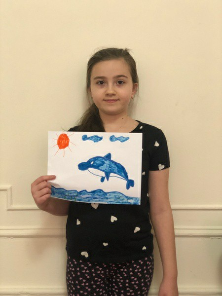 girl holds drawing of dolphin